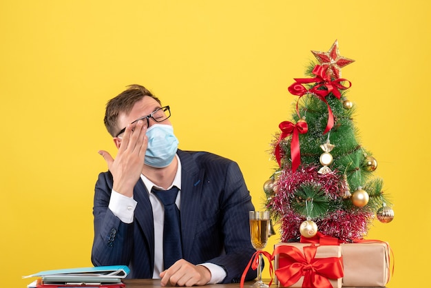 Front view business man covering his eye with hand sitting at the table near xmas tree and presents on yellow background