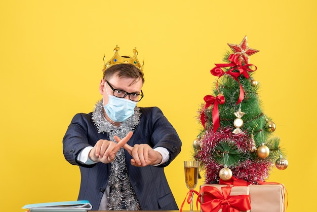 Front view business man crossing fingers sitting at the table near xmas tree and presents on yellow background