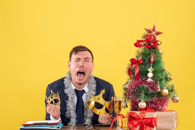 Uomo d'affari di vista frontale che piange mentre era seduto al tavolo vicino all'albero di natale e regali su sfondo giallo