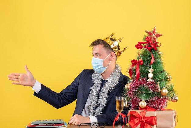 クリスマスツリーの近くのテーブルに座って手を差し伸べる正面図ビジネスマンと黄色の背景に提示