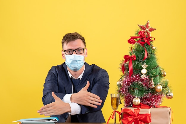 Front view of business man giving hands sitting at the table near xmas tree and presents on yellow