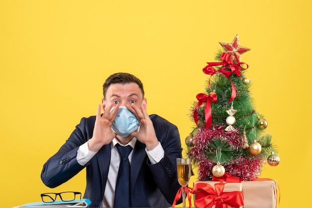 Vista frontale dell'uomo di affari che saluta qualcuno seduto al tavolo vicino all'albero di natale e presenta su giallo.