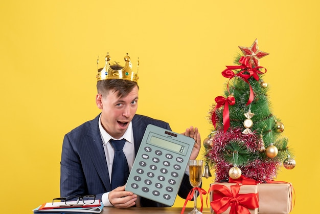 Front view of business man holding calculator sitting at the table near xmas tree and presents on yellow.
