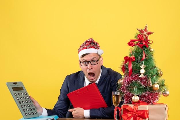 Vista frontale del calcolatore della holding dell'uomo di affari che si siede al tavolo vicino all'albero di natale e regali su colore giallo.