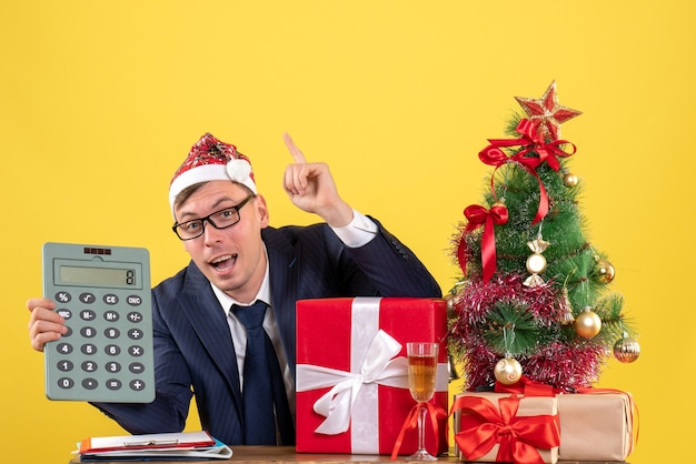 Vista frontale dell'uomo di affari che tiene l'albero di natale del calcolatore e regali su colore giallo.