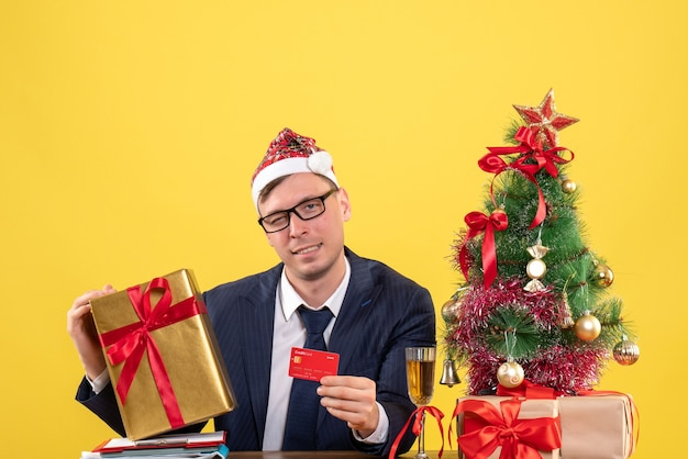 Vista frontale dell'uomo di affari che tiene la carta e il regalo di natale che si siedono al tavolo vicino all'albero di natale e regali su colore giallo.
