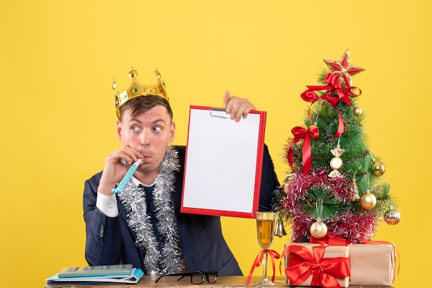 Front view of business man holding cliboard sitting at the table near xmas tree and presents on yellow.