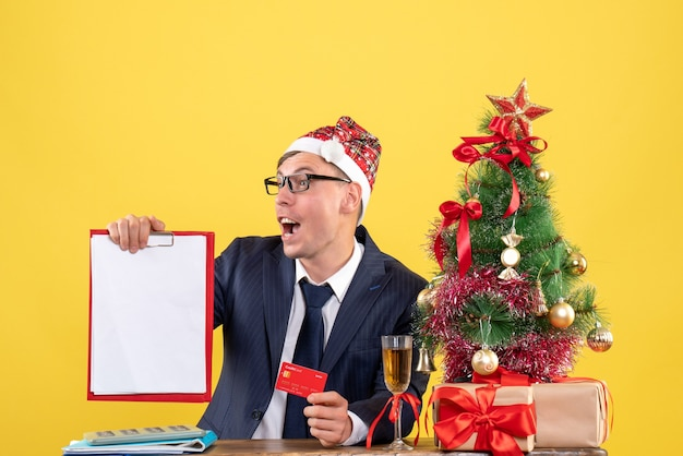 Front view of business man holding clipboard and card sitting at the table near xmas tree and presents on yellow