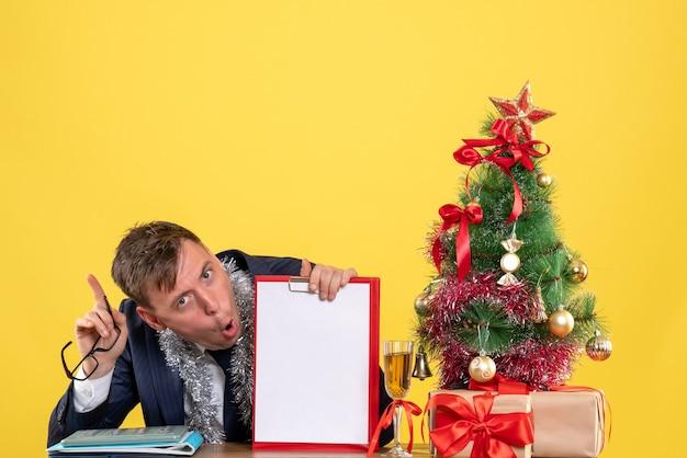 Vista frontale dell'uomo d'affari che tiene appunti e occhiali seduti al tavolo vicino all'albero di natale e regali su giallo