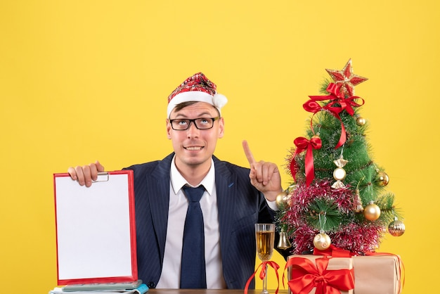 Front view of business man holding clipboard looking up sitting at the table near xmas tree and presents on yellow
