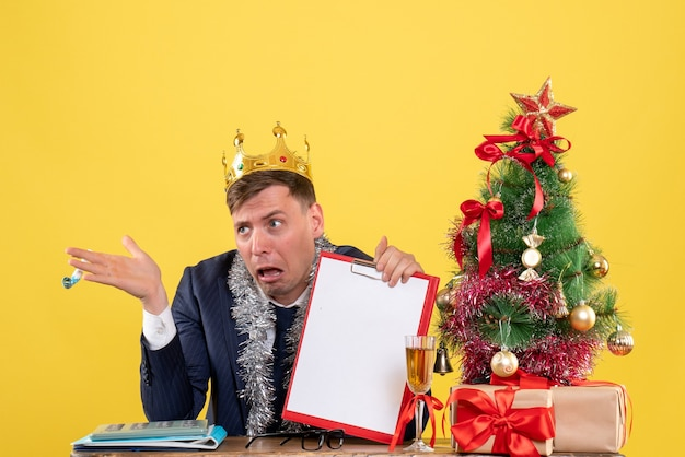 Front view of business man holding clipboard and noisemaker sitting at the table near xmas tree and presents on yellow