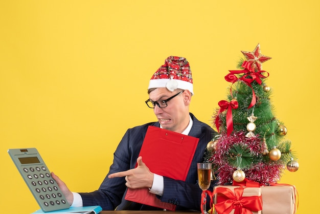 Front view of business man holding clipboard sitting at the table near xmas tree and presents on yellow