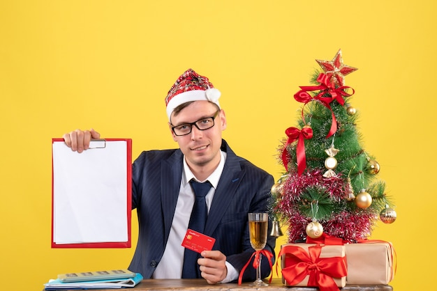Front view of business man holding credit card and clipboard sitting at the table near xmas tree and presents on yellow