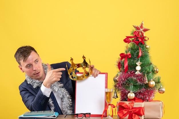 Vista frontale dell'uomo di affari che tiene corona e appunti seduti al tavolo vicino all'albero di natale e regali su giallo
