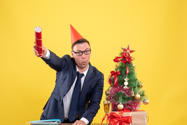 Vista frontale dell'uomo d'affari che tiene parte popper in piedi dietro il tavolo vicino all'albero di natale e presenta su giallo