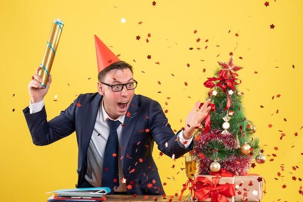 Vista frontale dell'uomo di affari che tiene il popper del partito che sta dietro il tavolo vicino all'albero di natale e presenta sul giallo