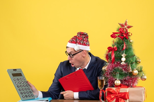 Front view of business man looking at calculator holding clipboard sitting at the table near xmas tree and presents on yellow