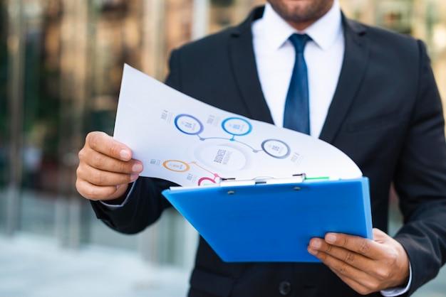 Вид спереди деловой человек, глядя на диаграммы