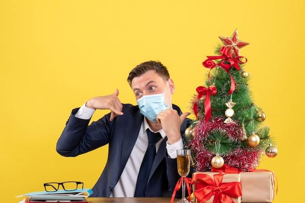 Vista frontale dell'uomo di affari che fa mi chiama il segno del telefono che si siede al tavolo vicino all'albero di natale e presenta su giallo