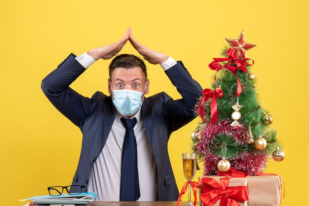 Front view of business man making hand roof over his head sitting at the table near xmas tree and presents on yellow