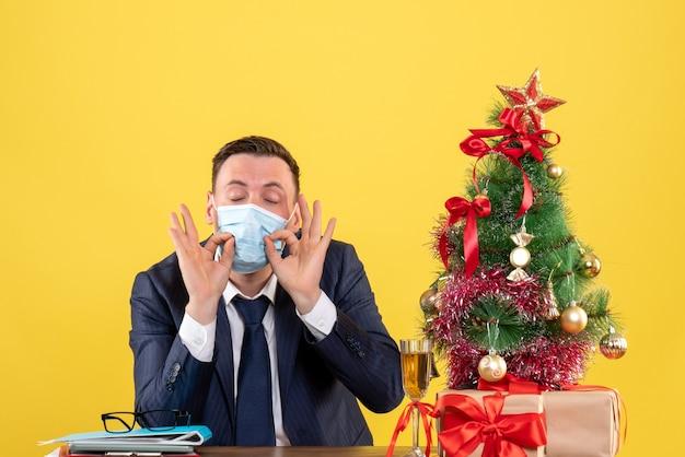 Vista frontale dell'uomo d'affari che fa segno okey davanti al suo viso seduto al tavolo vicino all'albero di natale e regali su giallo