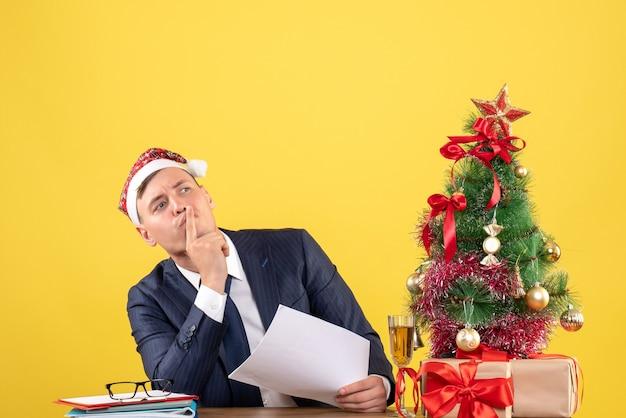 Vista frontale dell'uomo di affari che fa segno di shh che si siede al tavolo vicino all'albero di natale e regali su giallo