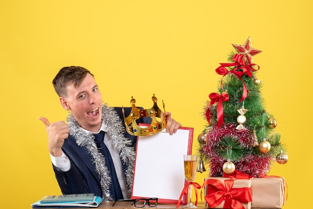 Front view of business man making thumb up sign sitting at the table near xmas tree and presents on yellow