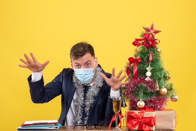 Front view of business man opening his hands sitting at the table near xmas tree and presents on yellow