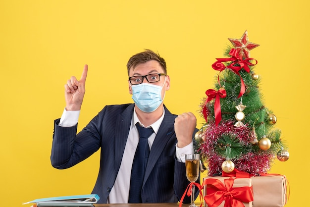 Vista frontale dell'uomo di affari che indica con il dito in su seduto al tavolo vicino all'albero di natale e regali su giallo