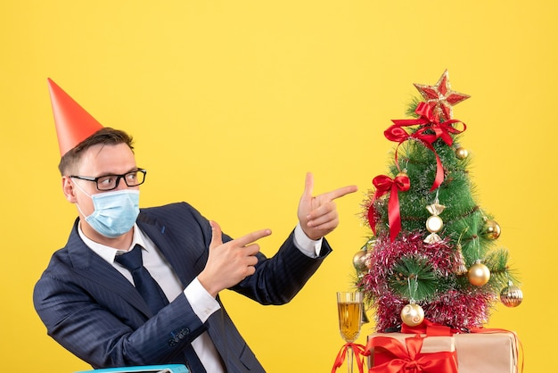 Front view of business man pointing at xmas tree and presents on yellow