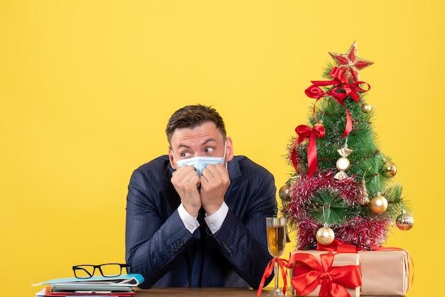 Vista frontale dell'uomo di affari che mette hadns al suo mento che si siede al tavolo vicino all'albero di natale e regali sul giallo