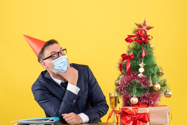 Front view of business man putting hand on his chin sitting at the table near xmas tree and presents on yellow