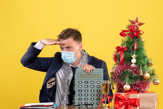 Front view of business man putting hand to his forehead sitting at the table near xmas tree and presents on yellow