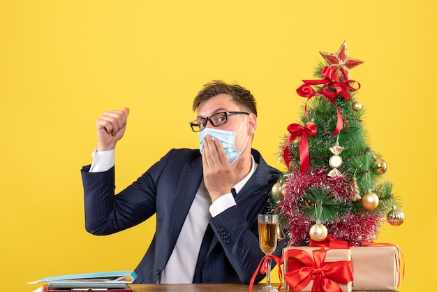 Front view of business man putting hand on his mouth sitting at the table near xmas tree and presents on yellow
