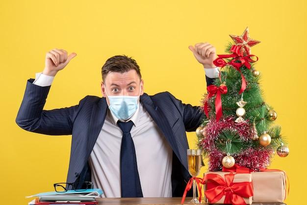 Vista frontale dell'uomo di affari che mette le sue mani in su che si siede al tavolo vicino all'albero di natale e regali su giallo