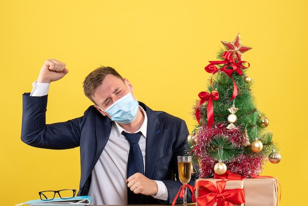 Front view of business man raising his hand sitting at the table near xmas tree and presents on yellow