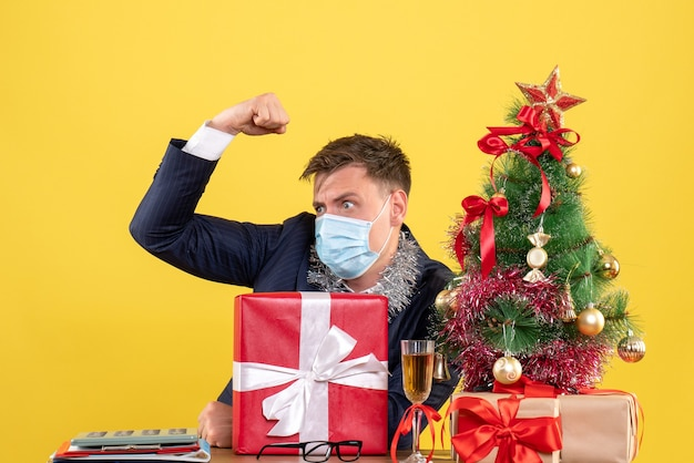 Front view of business man showing strength sitting at the table near xmas tree and presents on yellow.