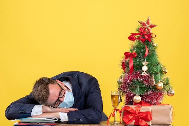 Front view of business man sleeping at the table near xmas tree and presents on yellow.