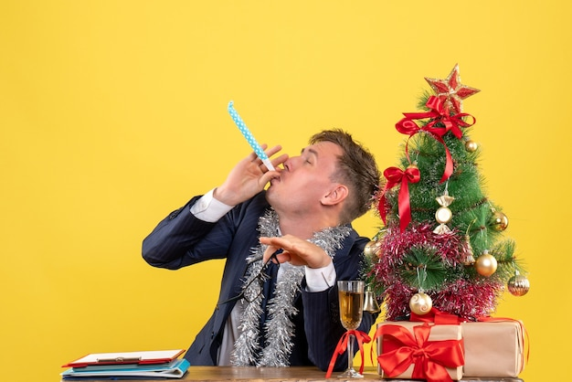 Front view of business man using noisemaker sitting at the table near xmas tree and presents on yellow