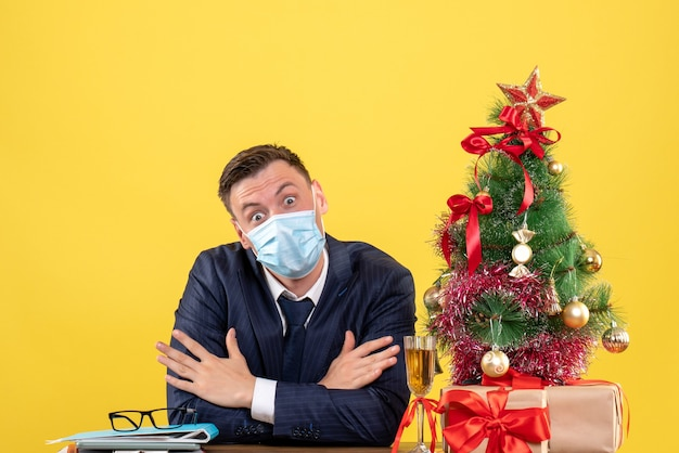 Front view of business man with crossed hands sitting at the table near xmas tree and presents on yellow