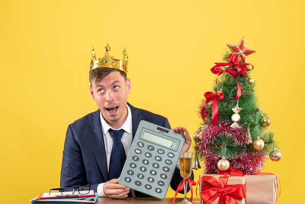 Front view of business man with crown holding calculator sitting at the table near xmas tree and presents on yellow