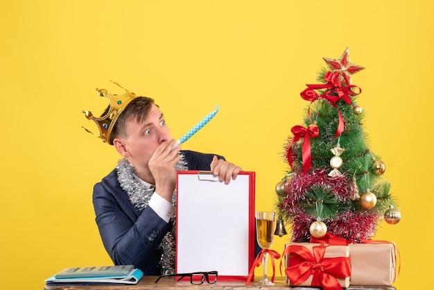 Vista frontale dell'uomo d'affari con la corona che tiene appunti utilizzando noisemaker seduto al tavolo vicino all'albero di natale e regali su giallo
