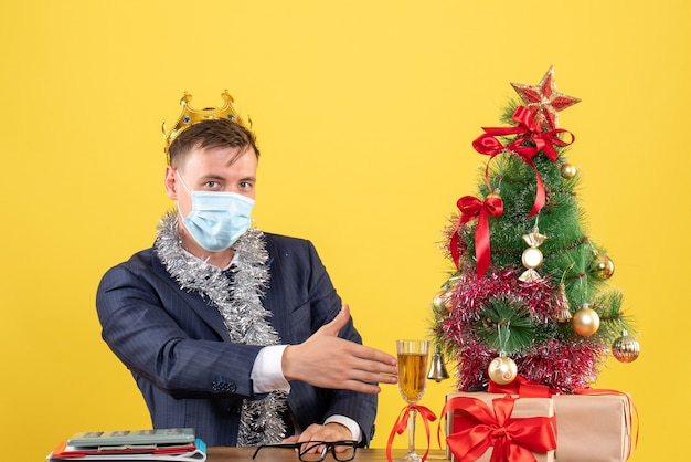 Front view of business man with mask giving hand sitting at the table near xmas tree and presents on yellow