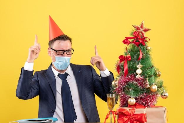 Vista frontale dell'uomo di affari con l'occhio ammiccante della mascherina medica che si siede al tavolo vicino all'albero di natale e regali sul giallo