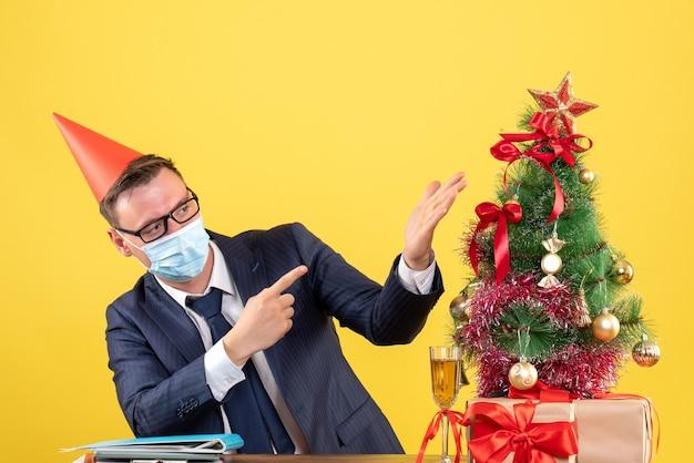 Vista frontale dell'uomo d'affari con mascherina medica che punta all'albero di natale e regali su giallo