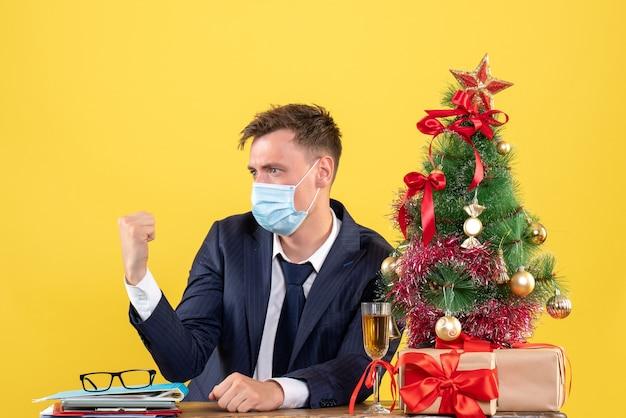 Vista frontale dell'uomo d'affari con mascherina medica seduto al tavolo vicino albero di natale e regali su giallo