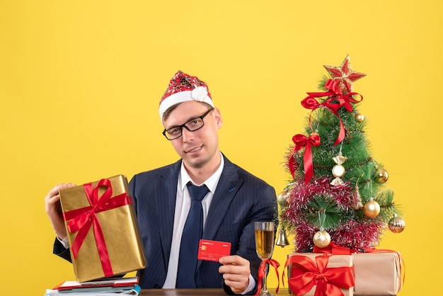 Front view of business man with santa hat holding card and gift sitting at the table near xmas tree and presents on yellow
