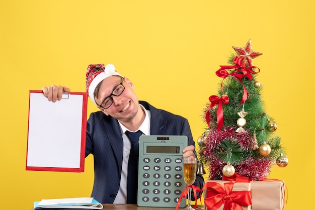 Front view of business man with santa hat holding clipboard and calculator sitting at the table near xmas tree and presents on yellow