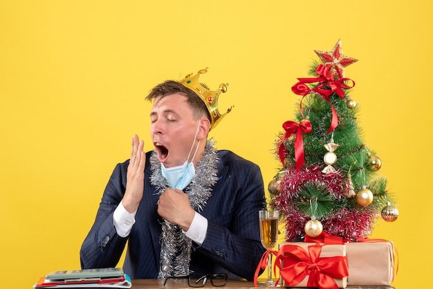 Front view of business man yawning sitting at the table near xmas tree and presents on yellow