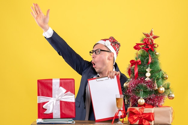 Front view of business man yelling at someone sitting at the table near xmas tree and presents on yellow